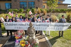 Children need heart-warming monumentsのスローガンを掲げて、慰安婦像の前で記念撮影