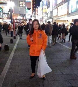 オレンジの作業着着用、ごみはさみ、ビニール袋をもつわたし