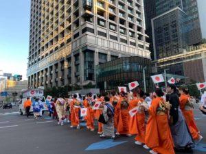 日の丸の小旗をもって和装でパレード