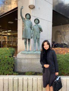 中央区立京橋築地小学校、小学生の像の前で