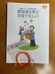 認知症サポーター養成講座標準教材と認知症サポーターキャラバンのオレンジリング(ブレスレット)