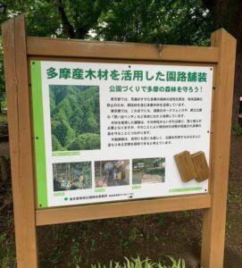 「多摩産木材を活用した園路舗装」を説明する木製掲示板